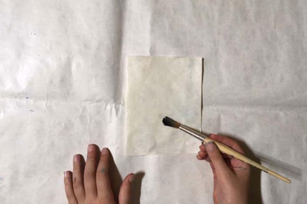 Lege das Packpapier mit der glatten Seite vor dich. Bestreiche die Seite dünn mit Tapetenkleister.