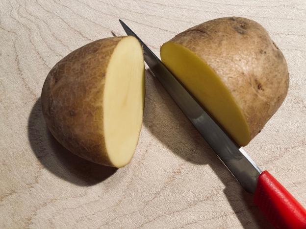 Halbiere die Kartoffeln mit dem Messer. Lass dir dabei eventuell helfen.