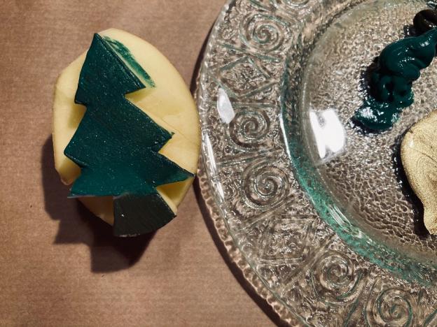 Nun gibst du die Farben auf einen Teller und streichst mit einem Pinsel dein Stempel-Motiv ein. Achte darauf, dass du nicht zu viel Farbe aufträgst – streife den Pinsel am Papier ein wenig ab.