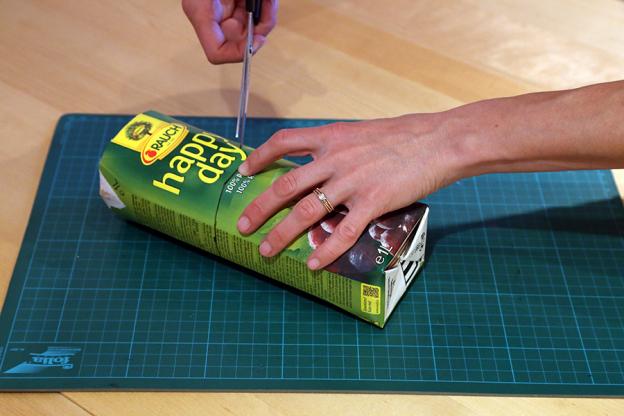 Schneide die Tetrapackung mit der Schere ungefähr in der Mitte auseinander. Lass dir dabei von einem Erwachsenen helfen, das geht nämlich gar nicht so leicht. Wir verwenden die untere Hälfte mit dem Boden.