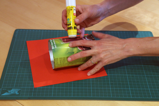 Schneide das rote Papier so zu, dass du die Tetrapackung rundherum damit bekleben kannst. An der offenen Seite der Tetrapackung kannst du ruhig etwas Papier überstehen lassen. Diesen Rand faltest du dann einfach nach innen um, dann sieht die Kante ganz besonders hübsch aus.