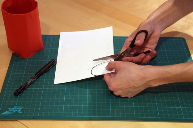 Zeichne nun mit Bleistift einen Bogen auf das weiße Papier und schneide ihn aus. Das wird das Gesicht des Nikolaus.