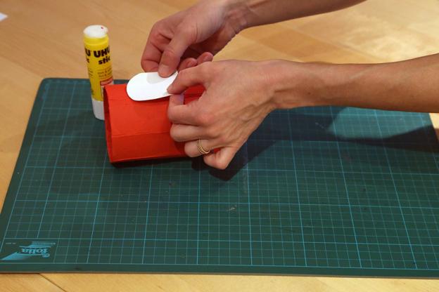 Klebe den weißen Bogen nun auf die Tetrapackung. Lass dabei etwa 4 cm Abstand zum oberen Rand.
