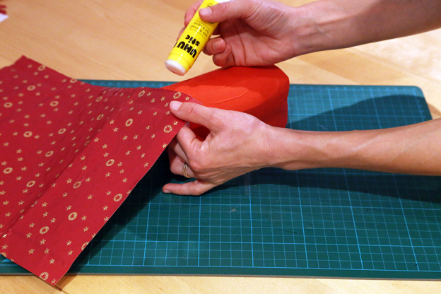 Schneide das Weihnachtsgeschenkpapier (oder jedes andere Papier, das du verwenden möchtest) so zu, dass es einmal rund um die Tetrapackung passt und etwa 30 cm hoch ist. Bestreiche dann den oberen Rand der Tetrapackung mit Kleber und befestige das Papier rundherum.