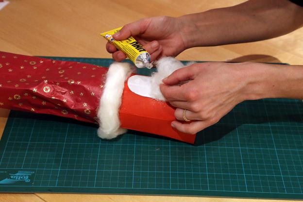 Mit Watte kannst du nun den Rand des Geschenkpapiers verzieren und das Gesicht des Nikolaus mit einem Bart und Haaren versehen.