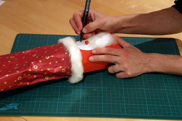 Mit Filzstift kannst du deinem Nikolaus nun Augen aufmalen. Forme aus einem kleinen Stückchen rotem Papier eine kleine Kugel. Das ist die Nase.