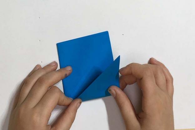 Schritt 3: Falte nun zuerst die rechte äußere Spitze nach oben, danach die linke.