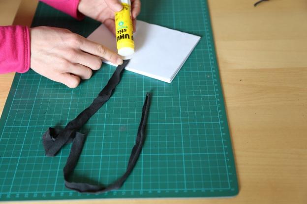 3. Bänder mittig auf die lange, äußere Seite des ersten bzw. letzten Kuverts kleben.