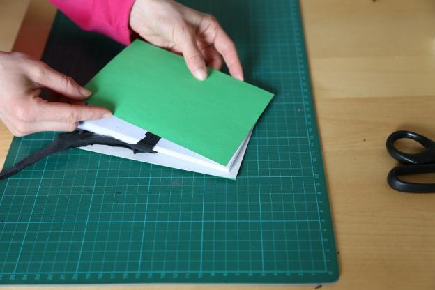 7. Kuvertblock zwischen die Buchdeckel legen und festkleben.