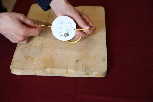 Als letzten Schritt schneide zwei Schnüre mit ca. 50 cm Länge ab und fädle sie links und rechts durch die Löcher.
