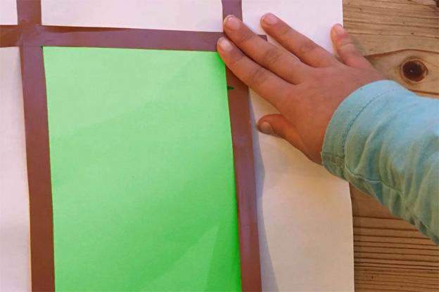 Lege nun den Bogen Papier auf eine Unterlage und klebe den Rand mit einem Klebestreifen ab.