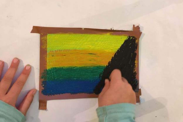 Jetzt übermale das Bild mit schwarzer Ölkreide. Das Schwarz soll dabei die anderen Farben völlig abdecken.