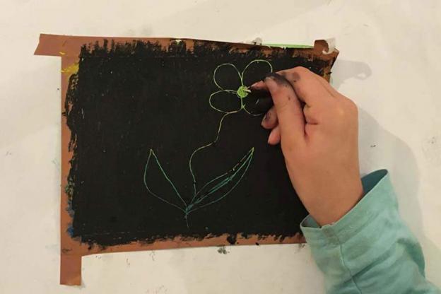 Nun kratze mit einem spitzen Gegenstand ein beliebiges Muster in das Bild. Du kannst natürlich auch etwas hineinschreiben. Tipp: Möchtest du etwas ausbessern, einfach mit schwarzer Ölkreide drüber malen und dann aufs Neue loskratzen.