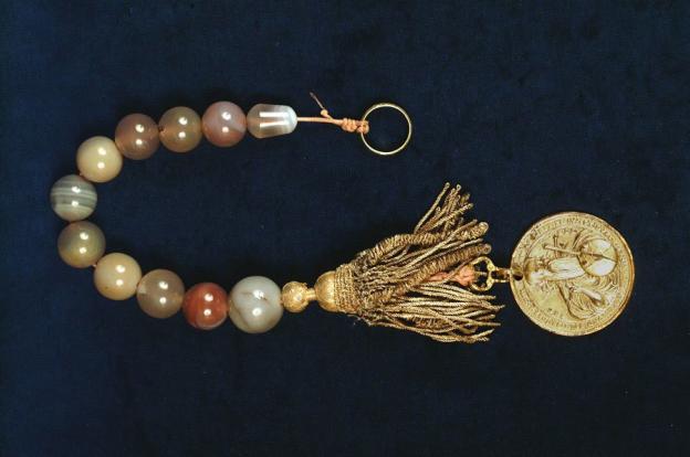 Rosenkranz, Zehner aus Achat, um 1600/1700, Länge 43 cm. Ein gezierter Herrenring oben und eine Medaille aus dem 16. Jh., mit Boullionquaste unten schließen die offene Kette ab.