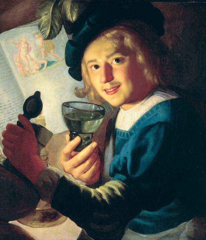 Ein junger Mann sitzt bei Tisch. Er hält ein volles Glas in seiner rechten Hand und hebt mit seiner linken einen Krug.