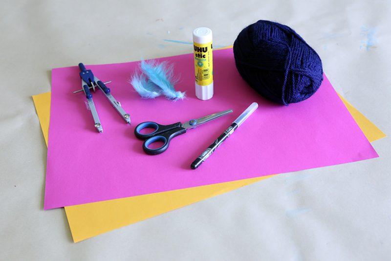 Auf dem Tisch liegt buntes Papier, ein Zirkel, Kunstfedern, Uhustic, Schere, Wolle und ein schwarzer Stift.