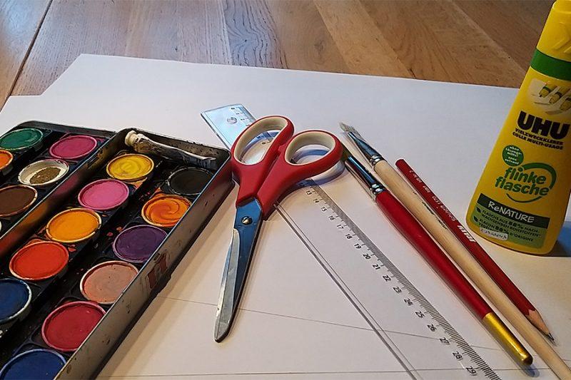Auf einem Tisch liegen Pinsel, Lineal, Kleber, Schere und Wasserfarben