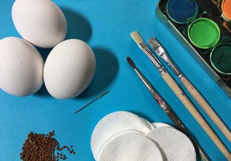 Auf einem Tisch liegen drei Eier, Pinsel, Wattepads, eine Nadel und Kressesamen.