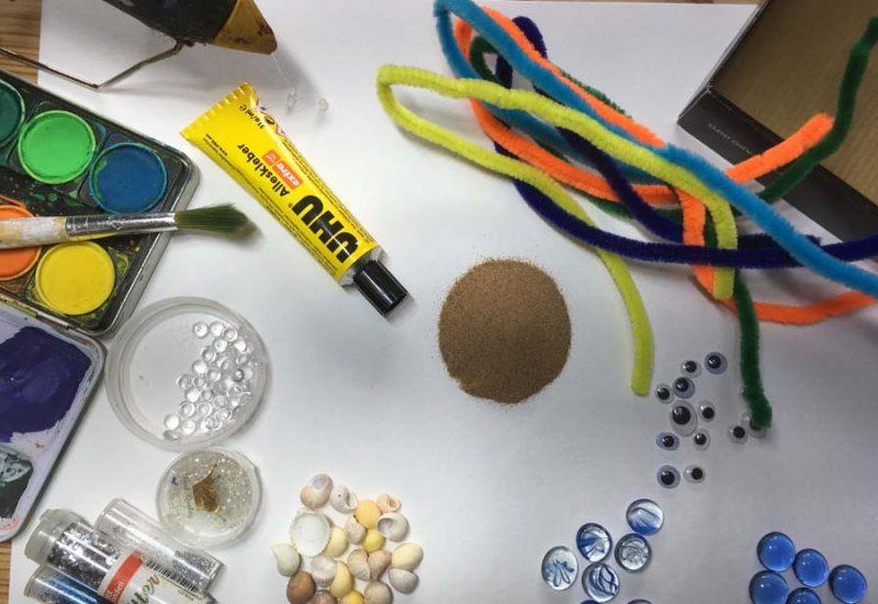 Auf dem Tisch liegen verschiedene Muscheln, Glassteine, Glitter, Wackelaugen, bunte Pfeifenputzer, Kleber und Heißklebepistole, Papier und Wasserfarben und der Deckel einer Schachtel.