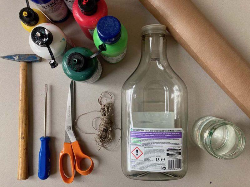 Auf dem Boden liegt ein großes Stück Packpapier, eine Plastikflasche, eine Schere, einen Hammer und ein Schraubenzieher, ein Stück Schnur, Farben (am besten Acryl- oder Wasserfarben) und genügend Wasser zum Verdünnen der Farben